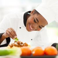 Beautiful african female chef garnishing spaghetti dish